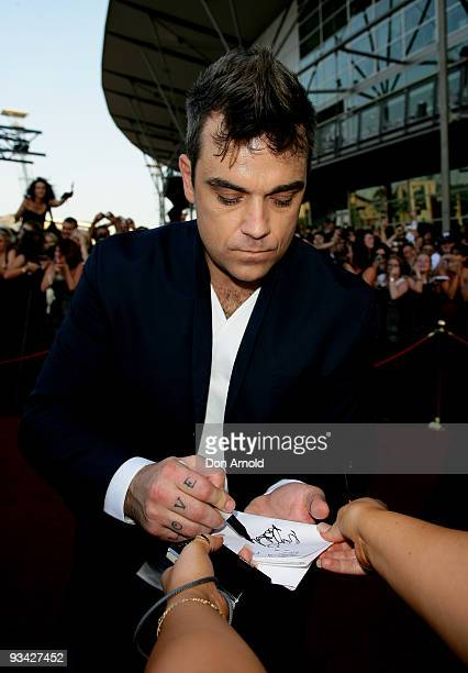 Singer Robbie Williams signs autographs as he arrives on the red carpet at the 2009 ARIA Awards at Acer Arena, Sydney Olympic Park on November 26,...