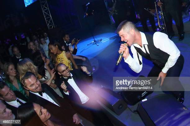 Singer Robin Thicke performs on stage as Leonardo DiCaprio and Rosario Dawson smile during amfAR's 21st Cinema Against AIDS Gala Presented By...