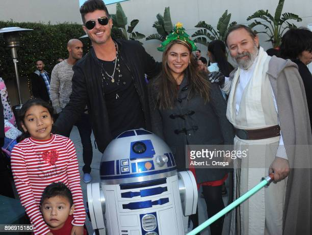 Singer Robin Thicke poses with children R2D2 and cosplayer Shawn Crosby as Luke Skywalker at A Children's Miracle Holiday Sponsored by Amity Medical...