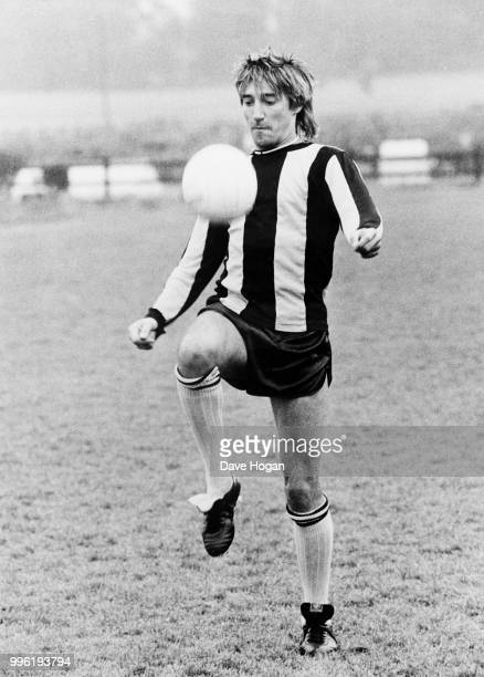 Singer Rod Stewart playing football in a striped shirt, possibly of Brentford FC, early 1980s.