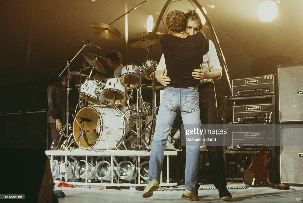 Singer Roger Daltrey (in black T-shirt) and guitarist Pete Townshend, of English rock group The Who, embrace on stage, circa 1979. In the background are bassist John Entwistle (1944 - 2002, left) and drummer Kenney Jones.