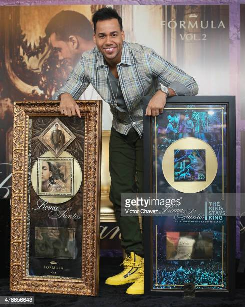Singer Romeo Santos poses with a gold disc for more than 30000 copies sold of his album 'Romeo Santos The King Stays King' and gold disc for more...
