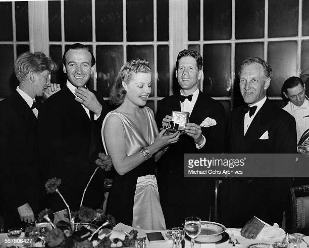 Singer Rudy Vallee presents a gift to Ann Sheridan with actors David Niven and Otto Kruger during an event in Los Angeles California