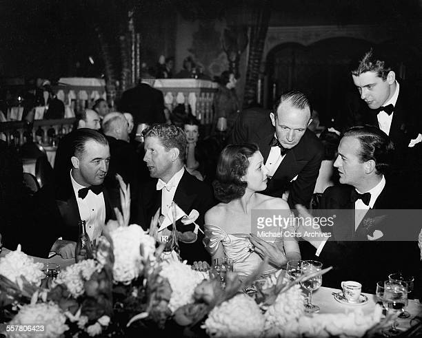 Singer Rudy Vallee sits with actress Loretta Young and actors David Niven and Richard Greene during an event in Los Angeles California
