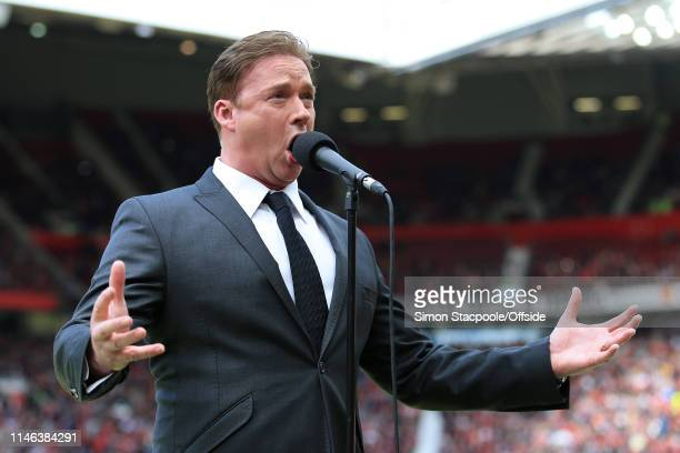 Singer Russell Watson performs during the Treble Reunion friendly match between the Manchester United '99 Legends and FC Bayern Legends at Old...