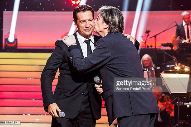 Singer Serge Lama kisses impersonator Laurent Gerra after they performed Gerra impersonating Lama during the live broadcast on public channel France...