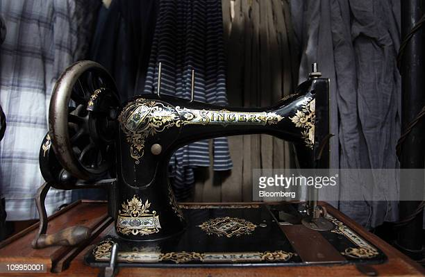 A Singer sewing machine stands against a backdrop of clothing in the window of an All Saints Retail Ltd store in London UK on Friday March 11 2011...