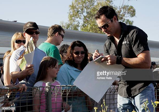 Singer Shannon Noll signs autographs for his fans following a performance at Broken Hill train station on December 3 2009 in Broken Hill Australia...
