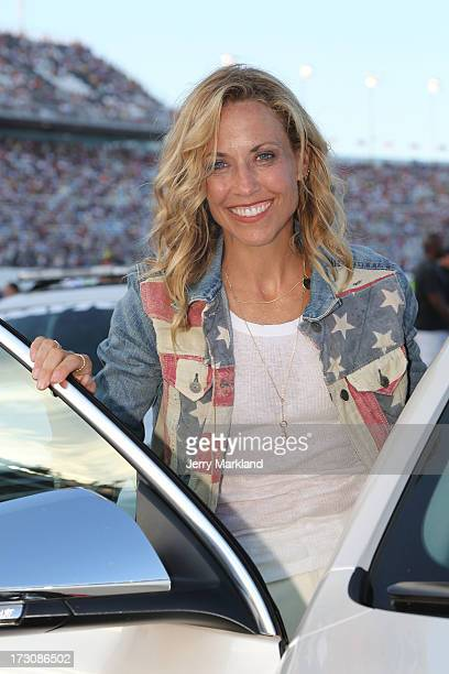 Singer Sheryl Crow smiles on the grid during the NASCAR Sprint Cup Series Coke Zero 400 at Daytona International Speedway on July 6 2013 in Daytona...