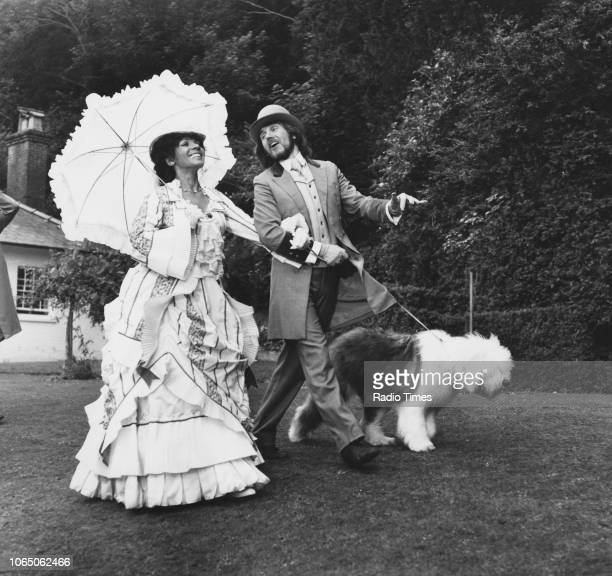 Singer Shirley Bassey wearing period costume as she films an outdoor scene with an actor and an Old English Sheepdog June 16th 1976