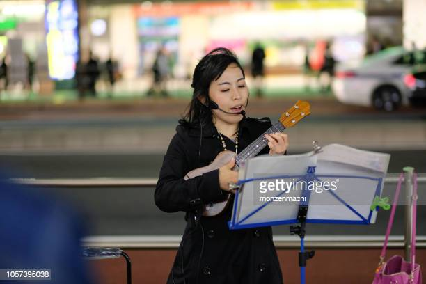 singer singing song on street - busker stock pictures, royalty-free photos & images