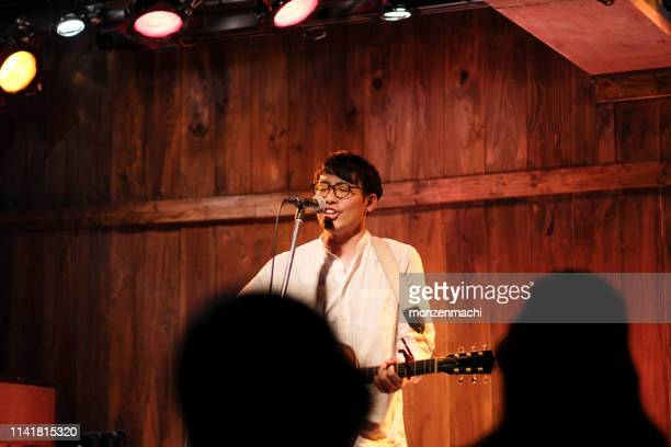 singer singing songs on stage - singer songwriter stock pictures, royalty-free photos & images