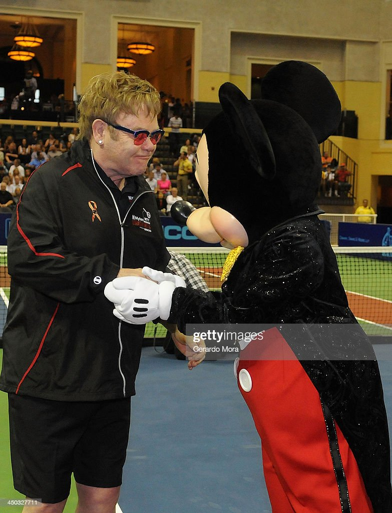 Singer Sir Elton John greets with Disney character Mickey Mouse during the Mylan World TeamTennis Matches at ESPN Wide World of Sports Complex on November 17, 2013 in Lake Buena Vista, Florida.