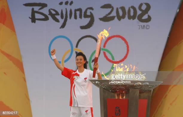 Singer Song Zuying, the last torchbearer of the day, lights the Olympic flame ending the second day of the Beijing leg of the Olympic torch relay at...