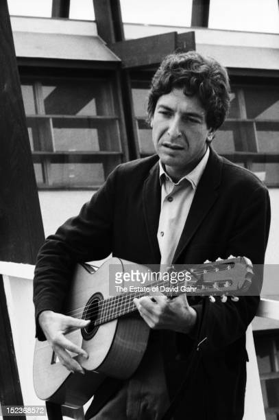 Singer songwriter and author Leonard Cohen poses for a portrait with his guitar backstage at the Newport Folk Festival in July 1967 in Newport Rhode...