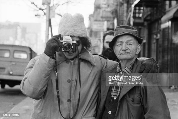 Singer songwriter Bob Dylan with a camera and a local denizen of New York City's Bowery District poses for a portrait on December 2 1971 on East 4th...