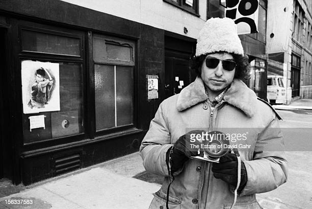 Singer songwriter Bob Dylan with a camera poses for a portrait on December 2 1971 on East 4th Street in the East Village New York City New York