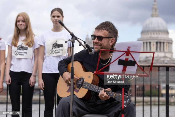 Singer, songwriter Damon Albarn joins Extinction Rebellion activists after unveiling a grass banner on the South Bank on June 25, 2021 in London,...