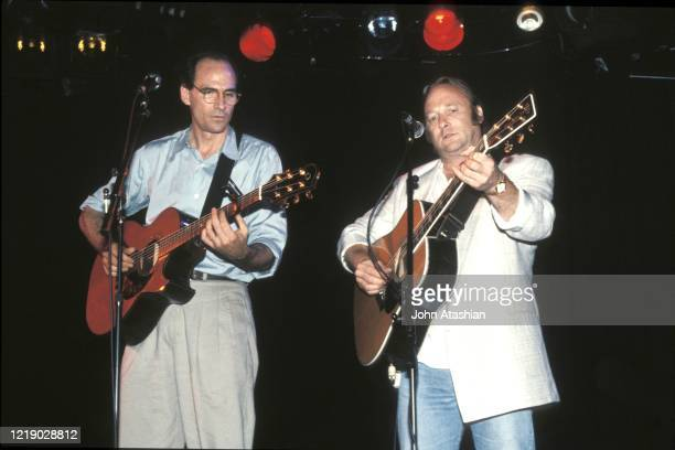 Singer songwriter guitarists James Taylor and Stephen Stills are shown performing on stage during benefit concert appearance on May 18 1991