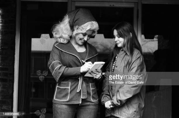 Singer songwriter musician and actress Dolly Parton signs an autograph for a fan before a performance on March 12 1977 at Bradley University in...