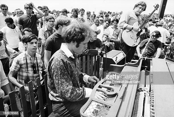 Singer songwriter Tim Hardin performs at the Newport Folk Festival in July 1966 in Newport Rhode Island Sharing the stage Harvey Brooks plays the...