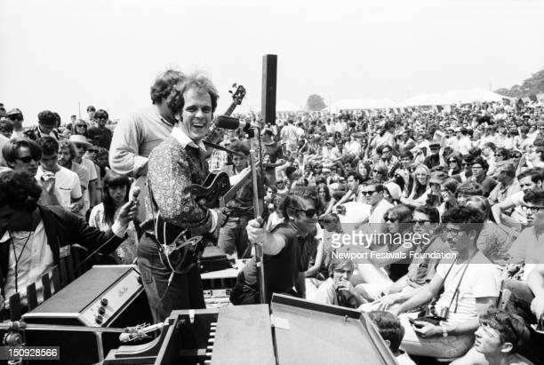 Singer songwriter Tim Hardin performs at the Newport Folk Festival in July 1966 in Newport Rhode Island Folk singer Bob Gibson holds up the...