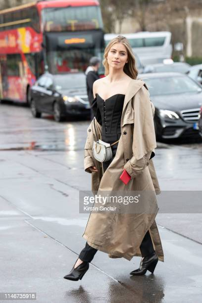 Singer Sophia Eve wears a Chloe bag, Walk of Shame trench, Saint Laurent trousers and top and Isabel Marant boots on March 02, 2019 in Paris, France.