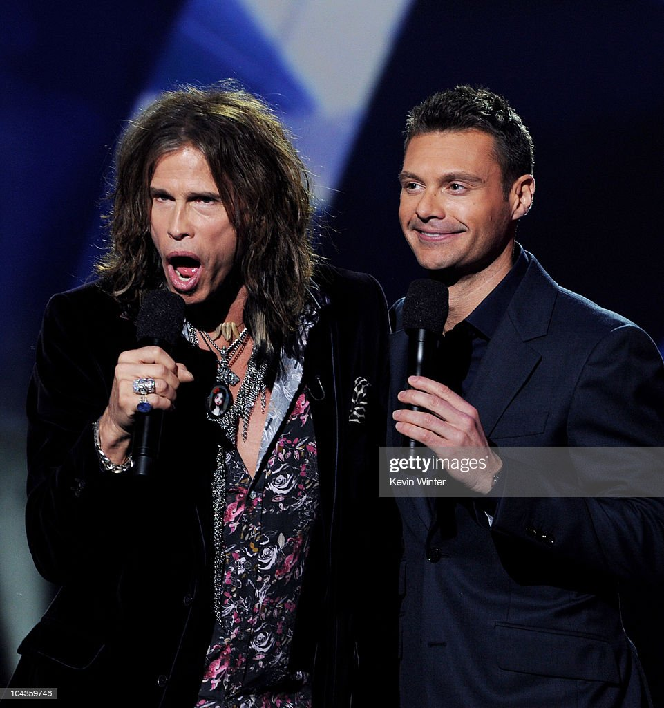 Singer Steven Tyler (L) and host Ryan Seacrest appear onstage at a press conference to officially announce the season 10 'American Idol' judges panel at The Forum on September 22, 2010 in Inglewood, California.