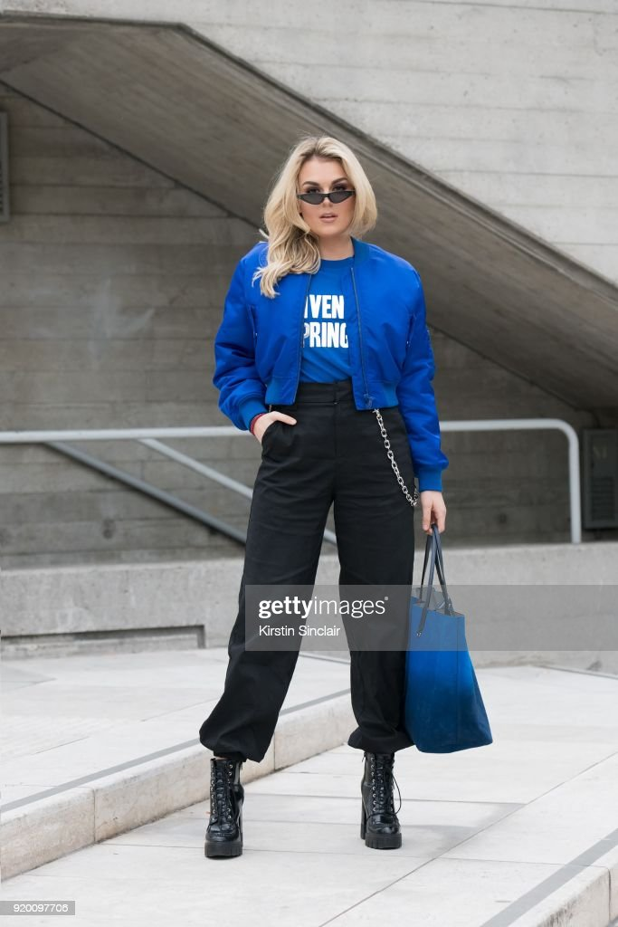 Singer Tallia Storm wears a Givenchy T shirt, jacket and bag, Zara boots, I.AM.GIA trousers and Poppy Lissiman sunglasses on day 3 of London Womens Fashion Week Autumn/Winter 2018, on February 18, 2018 in London, England.