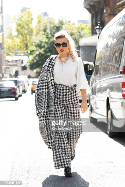 Singer Tallia Storm wears a Zara jacket trousers sunglasses and top with Bershka shoes during London Fashion Week September 2019 on September 13 2019...