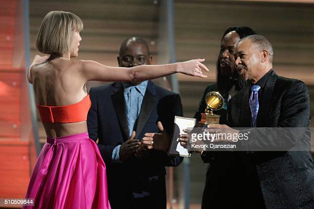 Singer Taylor Swift accepts the Album of the Year award for 1989 onstage from musicians Philip Bailey Verdine White and Ralph Johnson of Earth Wind...