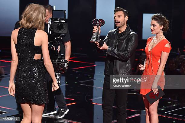 Singer Taylor Swift accepts the Artist of the Year award from TV/radio personality Ryan Seacrest onstage during the 2015 iHeartRadio Music Awards...