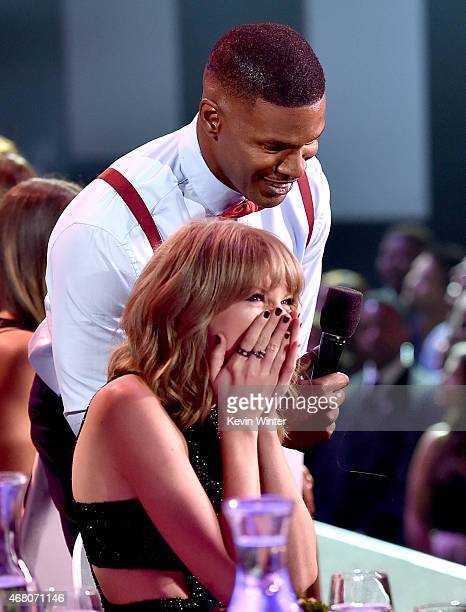Singer Taylor Swift and host Jamie Foxx speak at the 2015 iHeartRadio Music Awards which broadcasted live on NBC from The Shrine Auditorium on March...