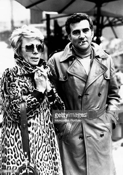 Singer Teddy Reno in a raincoat smoking in the company of Jula de Palma wearing a leopard print coat Rome 1974