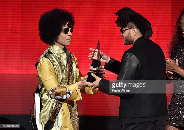 Singer The Weeknd accepts Favorite Soul/RB Album for 'Beauty Behind the Madness' from musician Prince onstage during the 2015 American Music Awards...