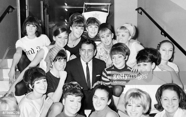 Singer Tony Bennett surrounded by chorus girls 7th November 1965