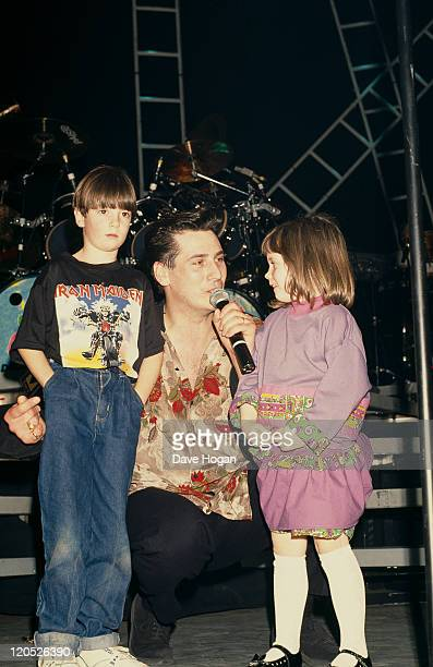 Singer Tony Hadley of British pop group Spandau Ballet singing to a boy and a girl circa 1985
