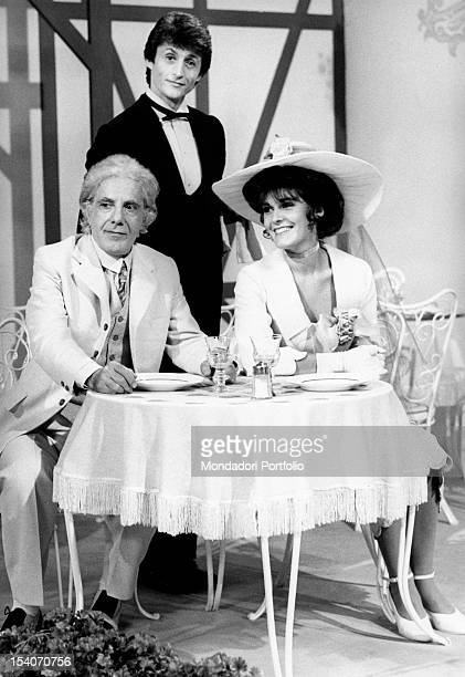 Singer Tony Renis in tight in the role of Leopold Brandmeyer head waiter standing between Gianrico Tedeschi in the role of Giovanni Pesamenole and...