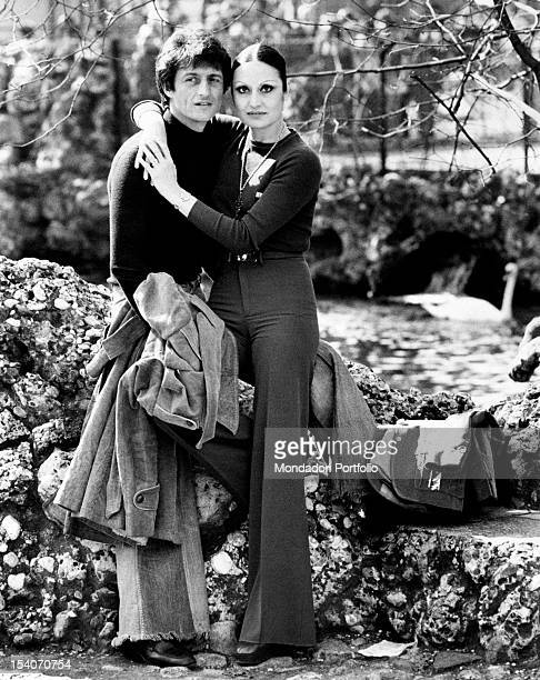 Singer Tony Renis posing for the photographer while he is hugged by his fiancee Elettra Morini at the public gardens Milan 1974