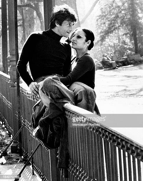 Singer Tony Renis sitting on a handrail about to kiss on the forehead his fiancee Elettra Morini at the public gardens Milan 1974