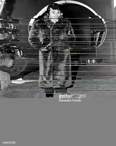 Singer Tony Renis while doing shopping wearing a showy fur coat Milan 1970