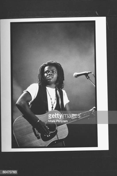 Singer Tracy Chapman playing guitar & singing on stage at Farm Aid V concert at Texas Stadium.