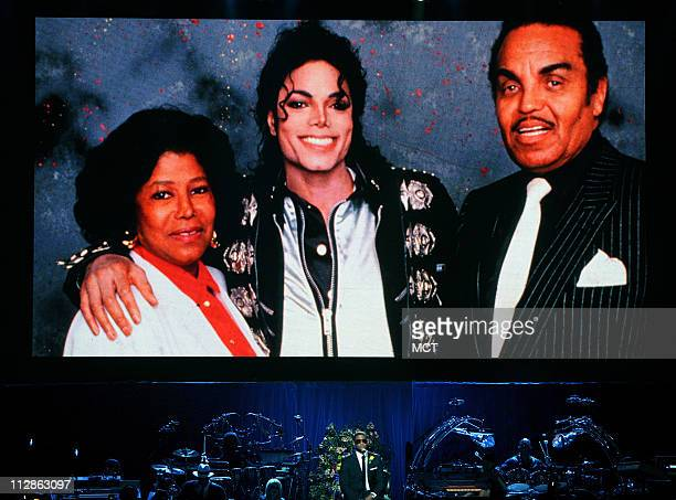 Singer Usher performs under a giant photo of Michael Jackson with his parents Katherine and Joe Jackson at a memorial service for the music legend at...