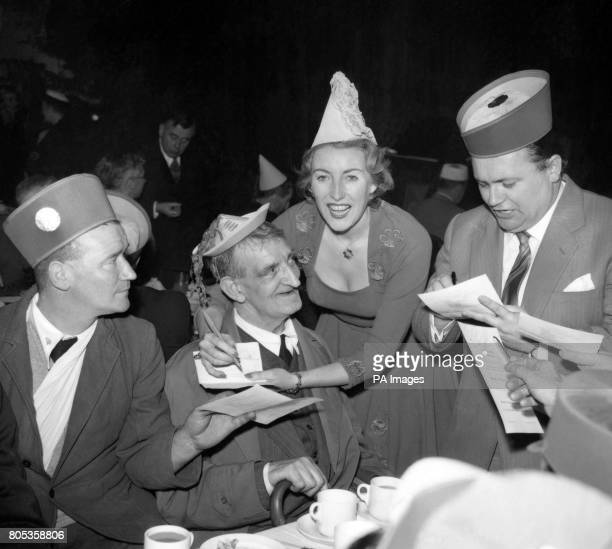 Singer Vera Lynn and comedian Harry Secombe right sign autographs at the tea tables during the 'Not Forgotten' Association annual Christmas party at...