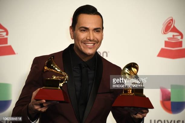 US singer Victor Manuelle poses with his awards for Best Salsa Album and Best Tropical Song in the press room during the 19th Annual Latin Grammy...