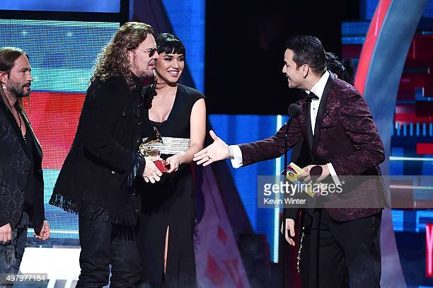 Singer Victor Manuelle presents musician Fher Olvera of Mana with the award for Best Pop/Rock Album for 'Cama Incendiada' onstage during the 16th...