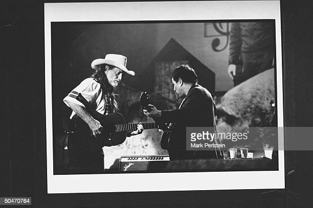 C/W singer Willie Nelson performing w singer Paul Simon both playing their guitars on stage during Farm Aid V concert at Texas Stadium