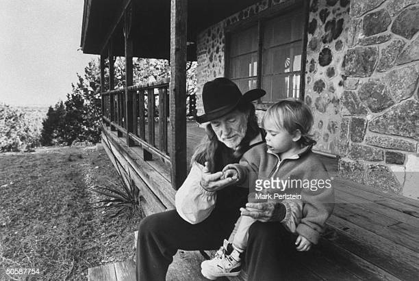 C/W singer Willie Nelson w his son Lukas Autry chatting as they sit on front steps of his barren cabin which the IRS stripped of its furniture after...