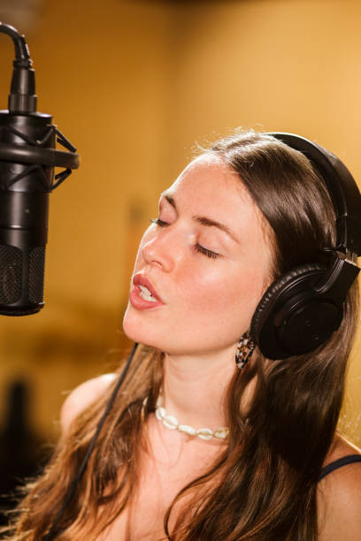 Singer with headphones at microphone in recording studio