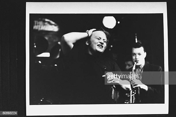 Singer/actor Andrew Strong w mike singing as he is backed up on saxophone by Felim Gromley while performing at party w the others from the movie The...